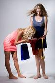 Mirada de dos niñas en un paquete de papel rojo para compras — Foto de Stock