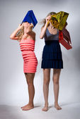 Two girls put on heads multi-colored packages for purchases — Stock Photo