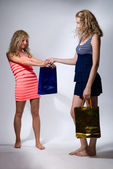 Two girls with paper packages for purchases — Stock Photo