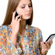 Young business woman with two mobile phones in talks. — Stock Photo