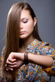 Lovely girl with long hair looks at clock — Stock Photo