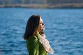 Thoughtful girl in a coat on the Water — Stock Photo