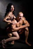 Muscular man and a woman posing in studio — Stock Photo