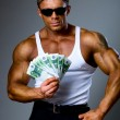 Handsome muscular man with euro banknotes in hand. — Stock Photo #15618973