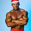 Strong athletic man in a cap of Santa Claus — Stock Photo #15619067