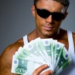 Handsome muscular man with euro banknotes in hand. — Stock Photo #15619253