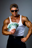 Handsome muscular man with euro banknotes in hand. — Stock Photo