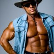Handsome muscular man in a cowboy hat — Stock Photo #15839653