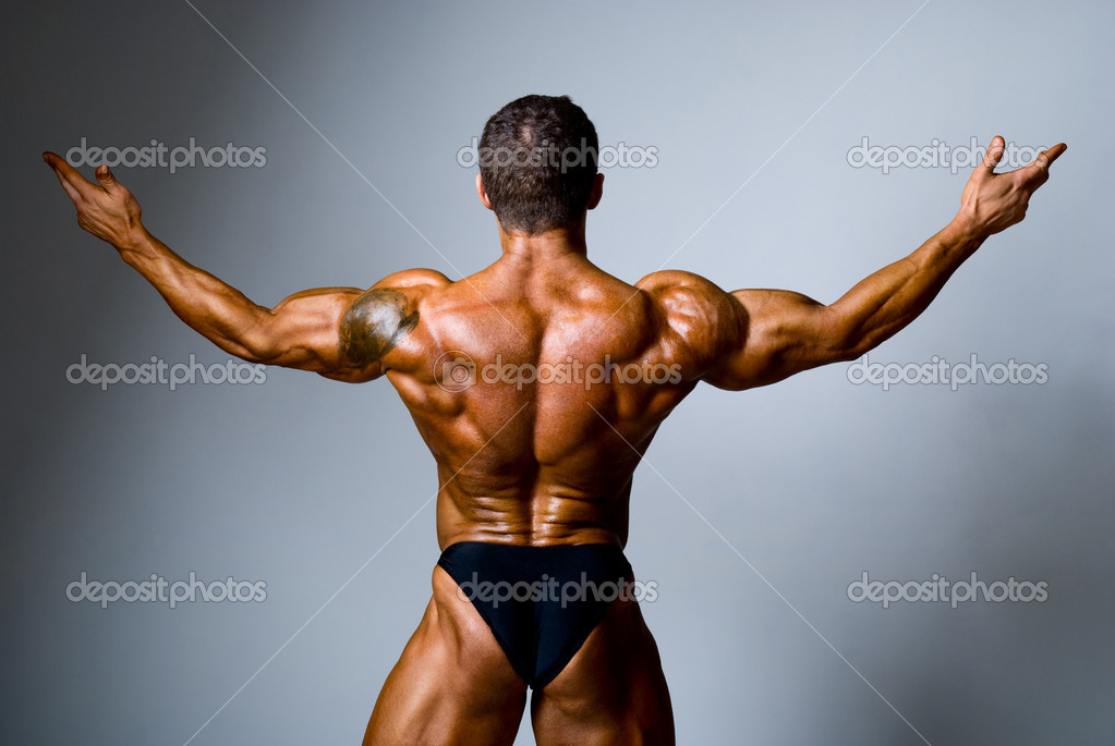 Young bodybuilder showing his biceps on a gray background  Stock Photo #15839613