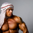 Muscular man wearing a middle eastern headdress - Foto Stock