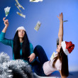 Girls in Santa hats, throw up banknotes — Stock Photo