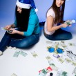Two girls in Santa hats believe banknotes — Stock Photo