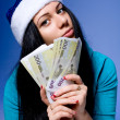 Girl in a Christmas hat holding euro banknotes — Stock Photo