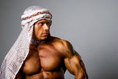 Muscular man wearing a middle eastern headdress — Stock Photo