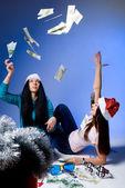 Girls in Santa hats, throw up banknotes — Stock Photo