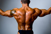 The back muscular man with a tattoo on her shoulder — Stockfoto