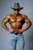Handsome muscular man wearing a hat and sunglasses — Stock Photo