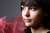 Close-up portrait of girl with red feathers — Stock Photo