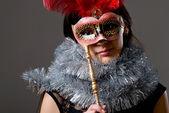 Close-up portrait d'une jeune fille dans un masque avec des plumes rouges et bidons — Photo