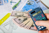 Calculator on a blurred background of the project and dollars — Stock Photo