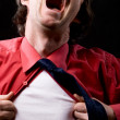 Enraged man rips off a red shirt - Stockfoto
