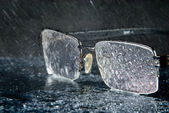 Rain and glasses lying on a mirror surface with water drops — Stock Photo