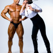 A woman with a pointer next to a bodybuilder — Stock Photo