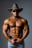 Muscular male in a hat and sunglasses — Stock Photo