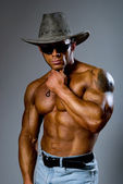 Muscular male in a hat and sunglasses on a gray background — Стоковое фото