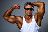 A strong man in sunglasses shows his muscles — Stock Photo