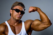A strong man shows his muscles. Trained body. The gray backgroun — Stock Photo