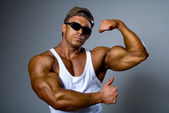 A strong man in sunglasses shows his muscles. Trained body. — Stock Photo