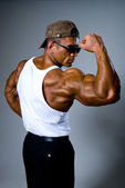 A strong man in sunglasses shows his muscles. — Stock Photo