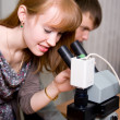 Female researcher looking through microscope — Stock Photo #23077122
