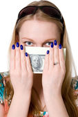 A young girl covers her face with a pack of dollars. — Stock Photo