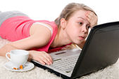 Young girl is lying on the floor and working on a laptop — Stock Photo