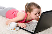 Tired girl with a laptop and a coffee cup — Stock Photo