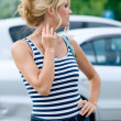 Beautiful girl waiting in the street against white cars — Stock Photo