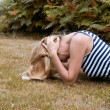Stock Photo: Girl lying on grass and brown hands clutching his head.