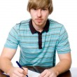 A young man sits at a desk with a pen in hand.  — Stock Photo