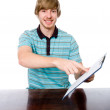 The young man points a finger at a blank sheet of sitting at the — Stock Photo #32473487