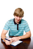 Cheerful young man sitting at a desk with a pen in hand. — Stockfoto
