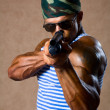 Strong athletic man with a gun. — Stock Photo