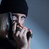 Young girl in a dark cap with a gun in his hand. with arms — Stock Photo