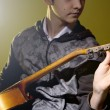 Stock Photo: Young msitting guitar tuning