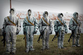 A group of soldiers with guns in their masks and protective clot — Stock Photo