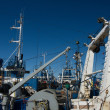 A messy view over fishing ships in a harbor - Stock Photo