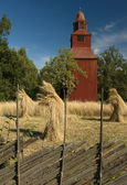 A traditional wooden church tower during summer harvest — Stock Photo