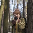 Woman in military uniform in the woods with guns - Stock Photo