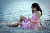 A girl in a summer dress resting on the beach at sunset — Stock Photo